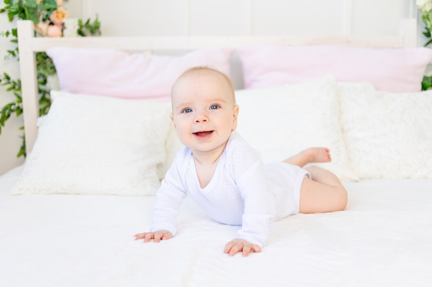 Szczęśliwa dziewczynka 6 miesięcy w białym body, leżąc na brzuchu na białym łóżku w domu