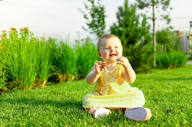 Szczęśliwa dziewczynka bawi się i spaceruje po zielonym trawniku latem w parku
