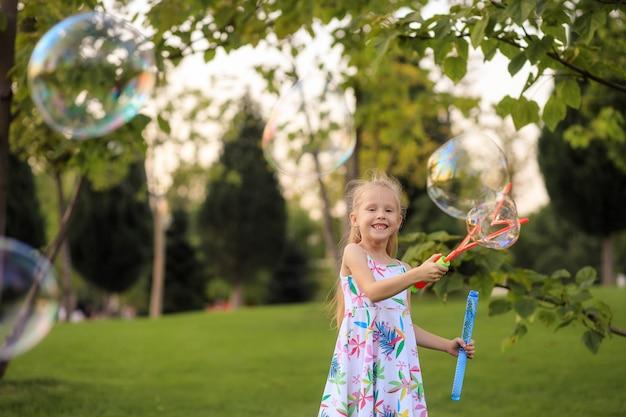 Szczęśliwa dziewczynka bawi się letnimi bańkami mydlanymi w parku.