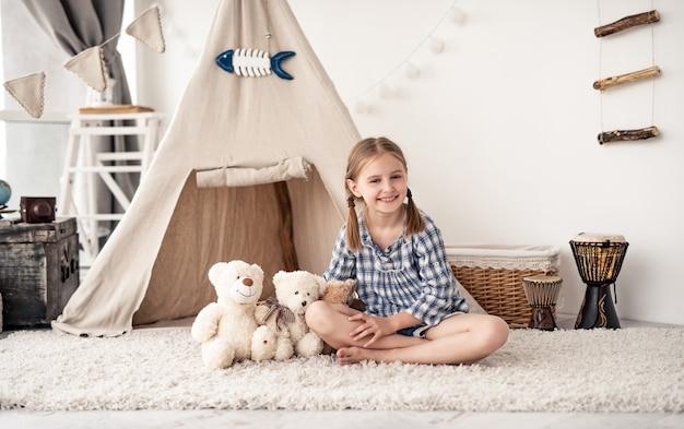 Szczęśliwa dziewczynka bawi się z misiami w pokoju z wigwamem