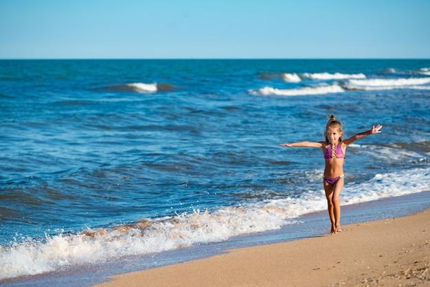 Szczęśliwa dziewczynka biegnie wzdłuż piaszczystego brzegu w pobliżu spokojnych fal morskich w słoneczny ciepły letni dzień
