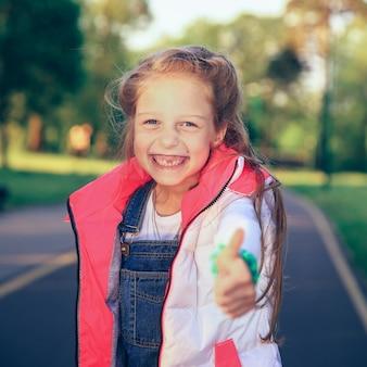 Szczęśliwa dziewczynka co kciuki do góry gest na spacer w parku w dzień wiosny