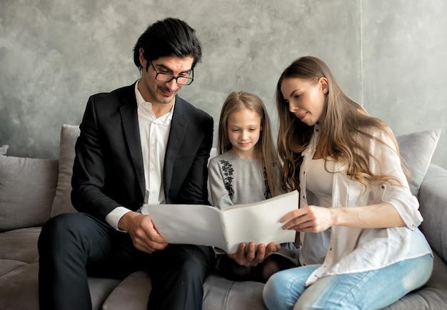 Szczęśliwa dziewczynka czyta książkę z rodzicami w domu