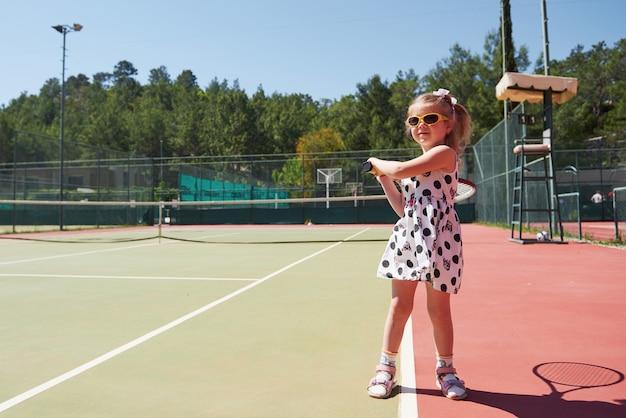 Szczęśliwa dziewczynka gra w tenisa. letni sport