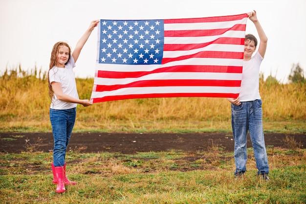 Szczęśliwa dziewczynka i chłopiec w białej koszulce, z amerykańską flagą.