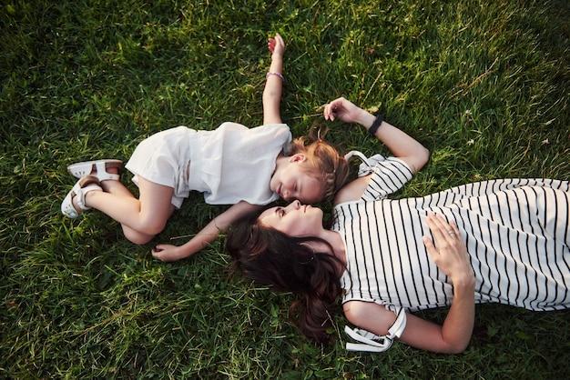 Szczęśliwa dziewczynka i jej matka, zabawy na świeżym powietrzu na zielonej trawie w słoneczny letni dzień.