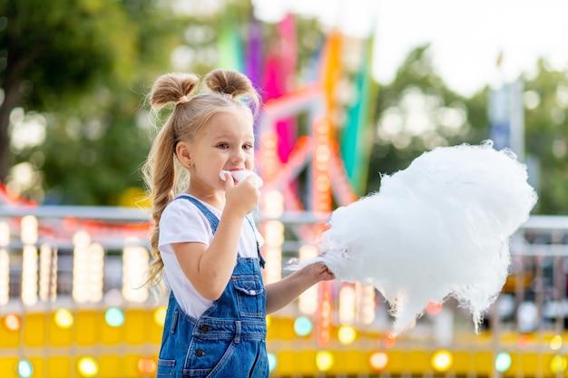 Szczęśliwa dziewczynka je watę cukrową w parku rozrywki latem