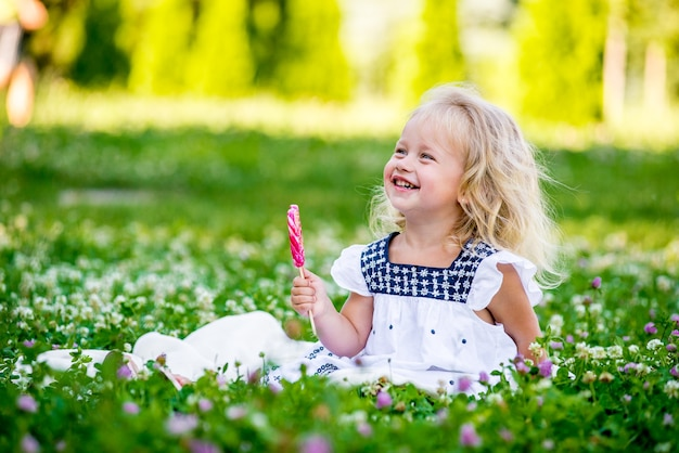 Szczęśliwa dziewczynka jedzenie cukierka na patyku w formie serca. koncepcja walentynki