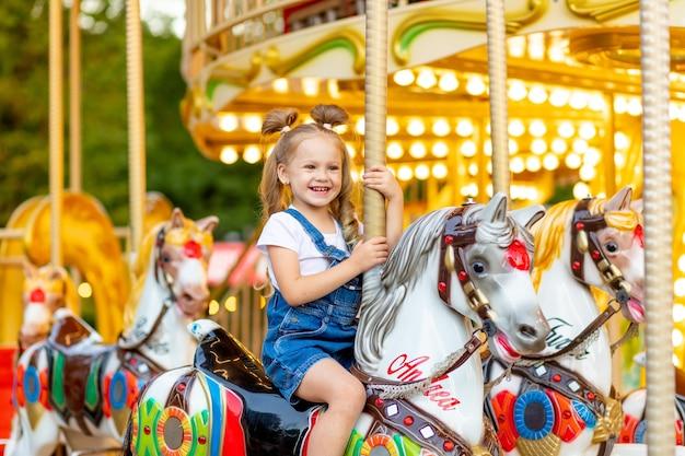 Szczęśliwa dziewczynka jedzie na karuzeli na koniu w parku rozrywki w lecie