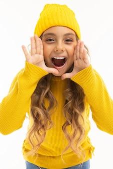 Szczęśliwa dziewczynka kaukaski w żółty kapelusz i bluza z kapturem na białym tle