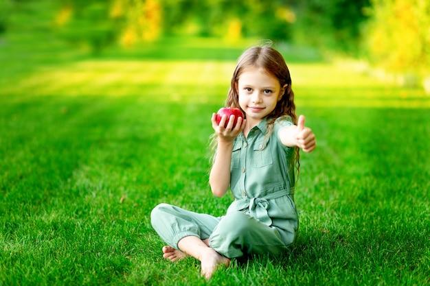 Szczęśliwa dziewczynka latem na trawniku z czerwonym jabłkiem na zielonej trawie i pokazuje klasę, miejsce na tekst