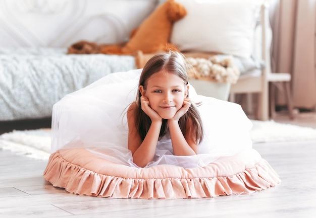 Szczęśliwa dziewczynka leży na podłodze w jasnej sypialni. spojrzenie w kamerę