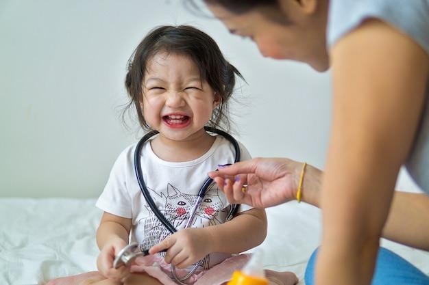 Szczęśliwa dziewczynka ma zabawę z matką w łóżku.