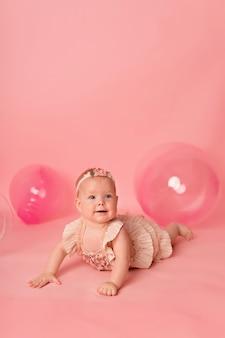 Szczęśliwa dziewczynka na różowym tle z balonami. uroczystość. urodziny