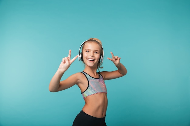 Szczęśliwa dziewczynka na sobie odzież sportową, słuchanie muzyki w słuchawkach na białym tle nad niebieską ścianą