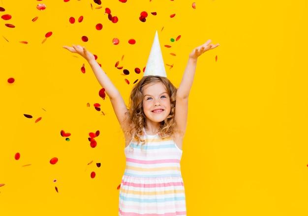 Szczęśliwa dziewczynka na żółtym tle studio, miejsce. portret pięknego dziecka bawiącego się błyszczącym konfetti