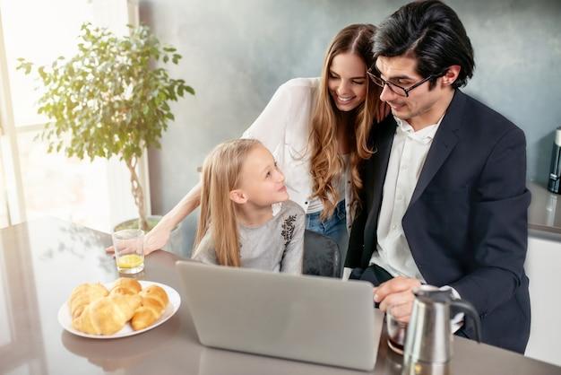 Szczęśliwa dziewczynka ogląda film na komputerze z ojcem i matką