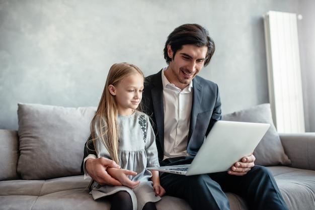 Szczęśliwa dziewczynka ogląda film na komputerze z ojcem w domu