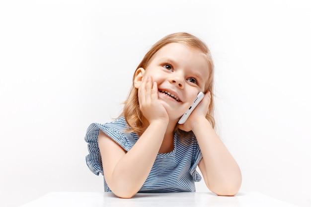 Szczęśliwa dziewczynka opowiada telefon komórkowego odizolowywającego na bielu. zbliżenie