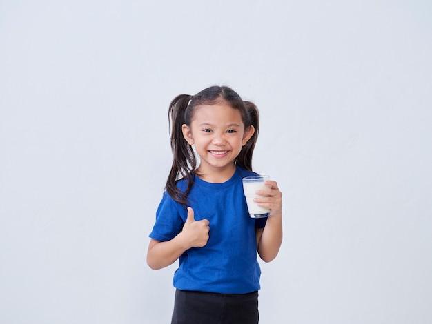 Szczęśliwa dziewczynka pije mleko i pokazuje kciuk znak przed światłem