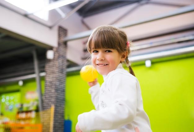 Szczęśliwa dziewczynka pozuje w ubraniach dla dzieci.