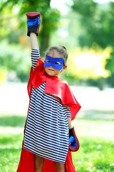 Szczęśliwa dziewczynka przebrana za superbohatera w rękawicach bokserskich w parku