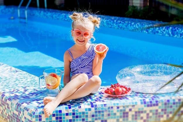 Szczęśliwa dziewczynka siedzi przy basenie w lecie picia lemoniady