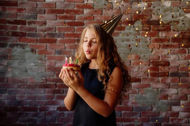 Szczęśliwa dziewczynka składa życzenie i zdmuchuje świeczki na torcie w dniu swoich urodzin