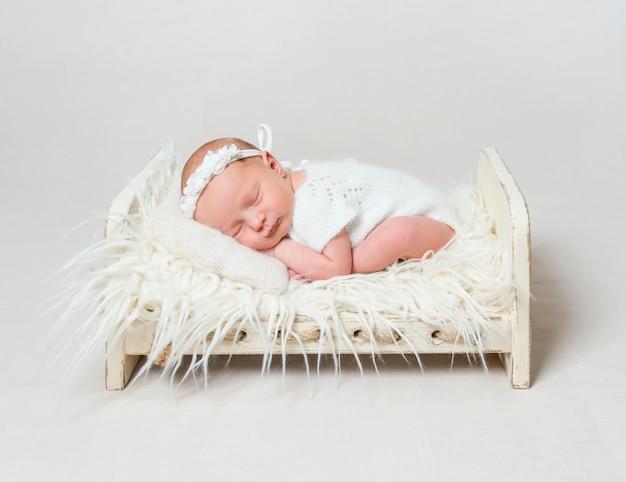 Szczęśliwa dziewczynka śpi na małym łóżeczku