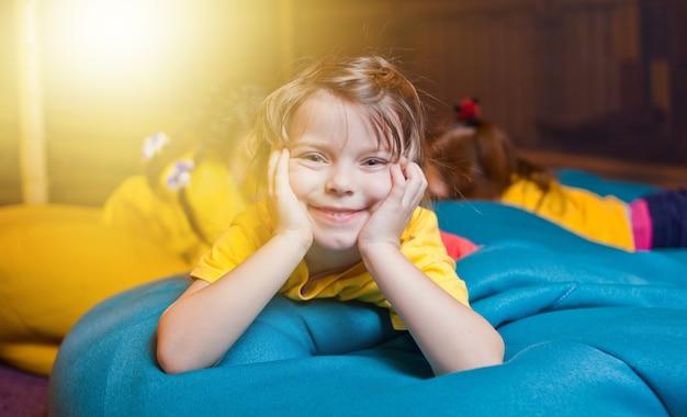 Szczęśliwa dziewczynka spoczywa na torbie krzesło w centrum rozrywki dla dzieci