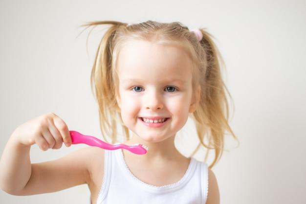Szczęśliwa dziewczynka szczotkowanie zębów, różowa szczoteczka do zębów, higiena jamy ustnej, poranna noc zdrowy styl życia koncepcja