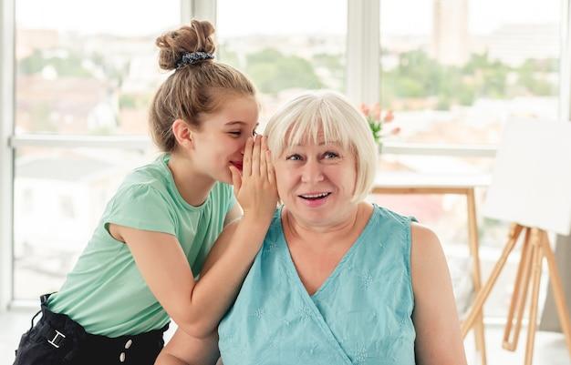 Szczęśliwa dziewczynka szepcze sekret uśmiechniętej babci w jasnym pokoju
