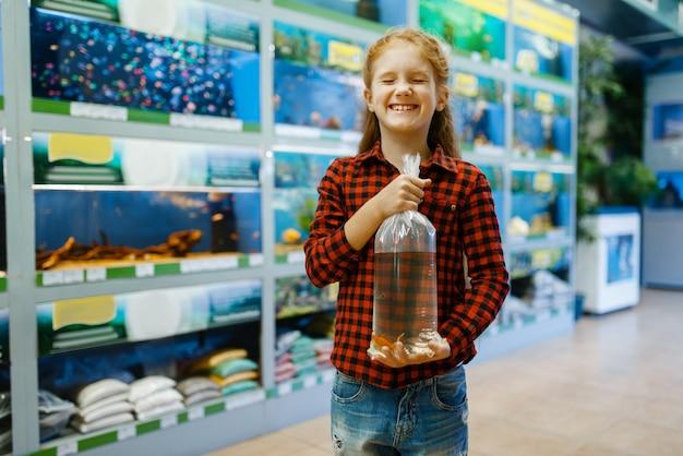 Szczęśliwa dziewczynka trzyma złotą rybkę i życzy sobie, sklep zoologiczny. kupowanie sprzętu dla dzieci w sklepie zoologicznym, akcesoria dla zwierząt domowych