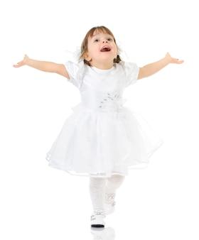 Szczęśliwa dziewczynka uśmiecha się i pozuje w białej sukni i butach, ręce rozłożone, jasnym tle do zdjęcia w pełnej długości