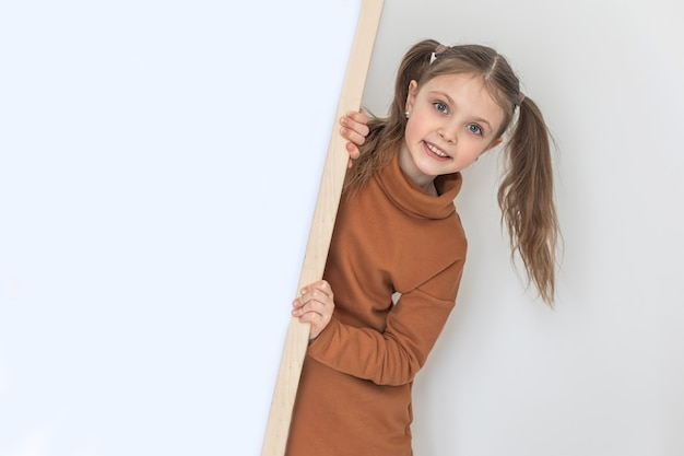 Szczęśliwa dziewczynka uśmiecha się i trzyma pustą deskę kreślarską, miejsce na test na białym backgraund