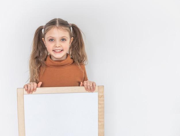 Szczęśliwa dziewczynka uśmiecha się i trzyma pustą deskę kreślarską, skopiuj miejsce do testu na białym backgraund