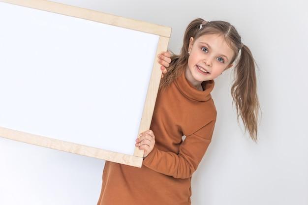 Szczęśliwa dziewczynka uśmiecha się i trzyma pustą deskę kreślarską z miejscem na kopię do testu na białym backgraund