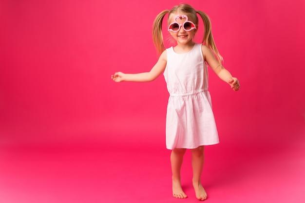 Szczęśliwa dziewczynka uśmiecha się w okulary na różowym tle