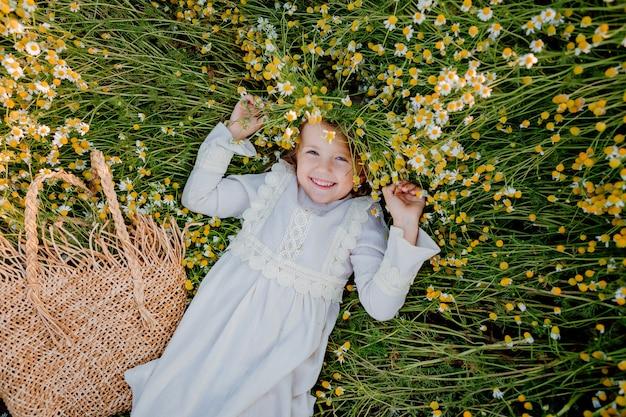 Szczęśliwa dziewczynka w bawełnianej sukience leży w polu stokrotek latem o zachodzie słońca. śmiech, widok z góry