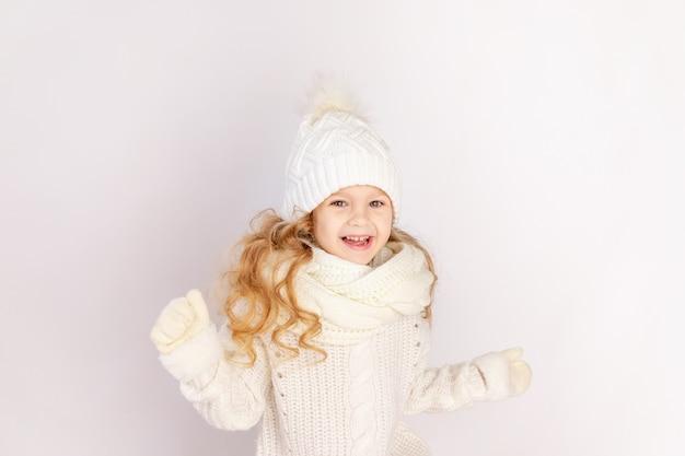 Szczęśliwa dziewczynka w ciepłym kapeluszu i swetrze na białym tle na białym tle, miejsce na tekst