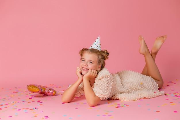 Szczęśliwa dziewczynka w czapce urodzinowej leży na różowym tle z konfetti, trzyma ręce na twarzy.