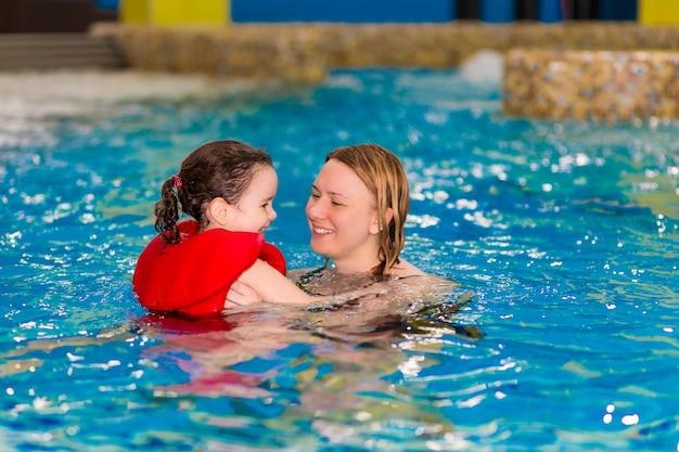 Szczęśliwa dziewczynka w czerwonej kamizelce pływa z matką w basenie parku wodnego