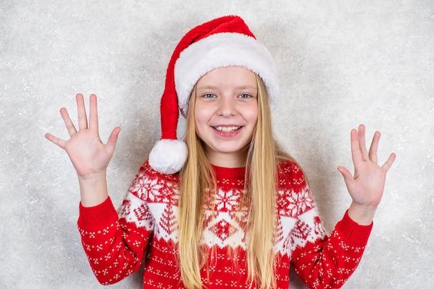 Szczęśliwa dziewczynka w czerwonym kapeluszu boże narodzenie. emocje