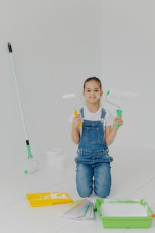 Szczęśliwa dziewczynka w drelichowych kombinezonach stoi na kolanach