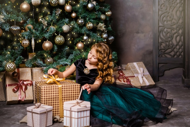 Szczęśliwa dziewczynka w fantazyjnym stroju siedzi obok choinki z obecnym pudełkiem. koncepcja boże narodzenie i nowy rok. zielono-złote kolory dekoracji.