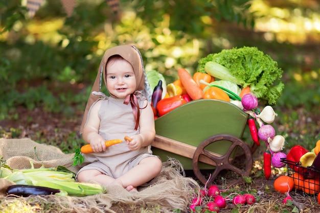 Szczęśliwa dziewczynka w garniturze zająca i marchewce w ręku na naturze zbiera plony warzyw