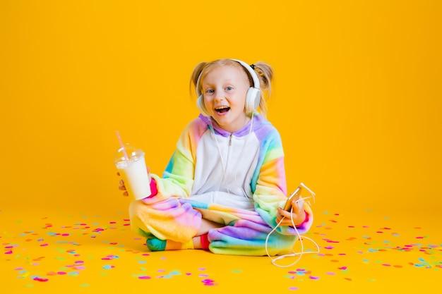 Szczęśliwa dziewczynka w jednorożcu kigurumi słucha muzyki w słuchawkach, trzymając smartfon