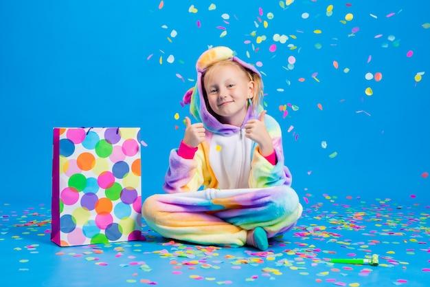 Szczęśliwa dziewczynka w jednorożcu kigurumi trzyma torbę na prezenty