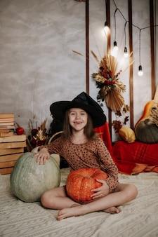 Szczęśliwa dziewczynka w kapeluszu wiedźmy siedzi na dzianym kocu z dyniami