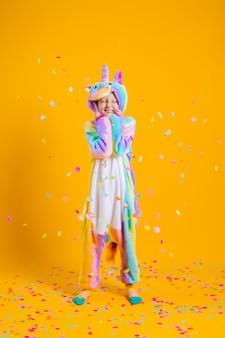 Szczęśliwa dziewczynka w kigurumi jednorożca, taniec na żółtej ścianie wśród wielokolorowych konfetti